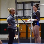 "Coach ""Wags"" gives Sophomore Brooklyn Beck some words of advice before Brooklyn competes her bar routine. Photo by Aislinn Menke"