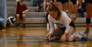 Senior Ally Huffman gets back up from the ground after diving to save the ball. Photo by Aislinn Menke