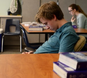 Senior Isaac Harnden plays a game on his phone during freetime. Photo by Luke Hoffman