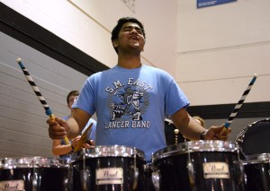 Senior Sid Choudhury plays the drums during the percussion part of the band's halftime show. Photo by Aislinn Menke