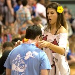 Senior Hazel Hitchcock places a Hawaiian lei around junior Jack Melvin's neck for the school theme. Photo by Luke Hoffman