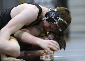 Junior Dane Erickson hooks his opponents leg and attempts to pin him. Photo by Katherine McGinness
