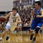 Sophomore Nick Arensberg dribbles the ball past a Rockhurst defender. Photo by Kate Nixon