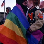 Two SMNW students laugh together while being wrapped in the LGBTQ+ pride flag. Photo by Lucy Morantz