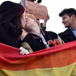 Two SMNW students kiss while holding the flag while their supporters stand with them. Photo by Lucy Morantz