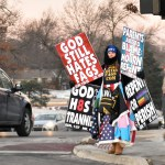 A Westboro Baptist Church protester stands on the corner of 75th and Mission holding defaming signs. Photo by Lucy Morantz