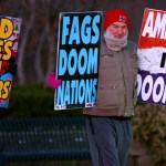 A member of the Westboro Baptist Church holds up anti-LGBT signs. Photo by Luke Hoffman