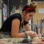 Sophomore Willa Ivancic sculpts her cylinder. Photo by Kathleen Deedy.