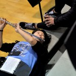 During third quarter, sophomore Olivia Hughes practices her flute while laying on the bleachers. Photo by Ellie Thoma