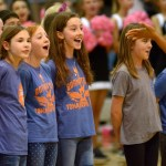 The student choir from Tomahawk Elementary School performs the national anthem to kick off the basketball game. Photo by Luke Hoffman