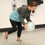 Senior Julia Stopperan runs to get the disco ball after it accidentally fell from the ceiling. Photo by Luke Hoffman