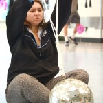 Senior Grace Chisholm tries to secure the rope holding the disco ball so it doesn't fall down once again. Photo by Luke Hoffman