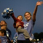 Sophomore Julie Fromm holds her little lancer and waves to the student section. Photo by Kate Nixon