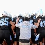 Senior Jack Melvin stands behind the team before they run out onto the field. Photo by Luke Hoffman