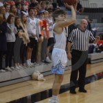 Senior, Noah Kurlbaum shoots a three pointer while the student section cheers him on. Photo by Taylor Keal.