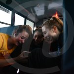 Sophomore Hanna Robinett, seniors Madison Mustoe and Taylor Fort, and sophomore Anabelle Merchant all laugh at a meme on the bus ride to Shawnee Heights Middle School. Photo by Megan Biles