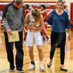 After twisting her elbow, Junior Kathleen Stanley walks off the court with the aide of Jv head coach Drew Steffan and Varsity head coach Lauren Lawrence. Photo by Megan Biles