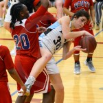 Sophomore Sarah Bingham goes up and gets the rebound but gets squished between two Wichita South defenders. Photo by Megan Biles