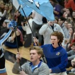 Senior Luke Cleaver runs out with the flags to start off the pep assembly. Photo by Julia Percy
