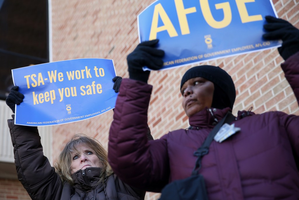 TSA workers Elizabeth Hughes, left, of Williamstown, N.J., and Francesca Saoudi, of Sharon Hill, Pa., hold signs during a rally against the government shutdown outside Philadelphia International Airport in Philadelphia on Friday, Jan. 25, 2019. Local members of Congress and furloughed government employees called for an end to the shutdown as workers missed another paycheck Friday.