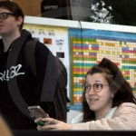 Sophomore Mary Scimeca glances up from her phone to watch junior Lucia Barraza perform. Photo by Kate Nixon