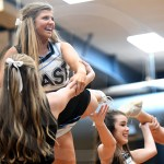 Senior Maggie Gray smiles at the crowd as she flies during a time out. Photo by Grace Goldman