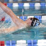 Junior Werner Brundige swims his 100-yard backstroke race. Brundige dropped 0.51 seconds to make his time 57.42 earning him tenth place in his event. Photo by Luke Hoffman