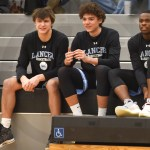 Boys Varsity Basketball players senior Noah Kurlbaum, sophomore Preston Reynolds, and junior Tony Friends watch the girls' varsity team face off against Free State prior to their own game. Photo by Luke Hoffman