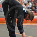 Senior Dane Erickson stretches his hamstrings before his match. Photo by Taylor Keal