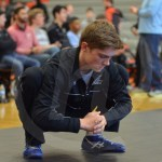 Senior Dane Erickson stretches his hip flexors in preparation for his match. Photo by Taylor Keal