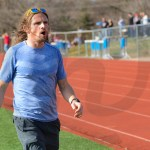 Coach Hacker yells from the sideline in the last stretch of a race. Photo by Annakate Dilks