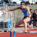 Senior Lucy Hoffman jumps over the hurdle during the girls 100 hurdles. Photo by Megan Biles