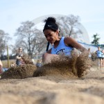 Senior Lauren Winston slides trough the sand as she completes the triple jump. Photo by Katherine McGinness
