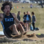 Junior Peter Kohring lands in the sand after completing his long jump. Photo by Elle Karras