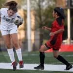 Sophomore Jilli Foley heads the ball towards the sideline to a teammate. Photo by Aislinn Menke