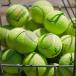 A basket of tennis balls sits beside the court awaiting to be used in a game. Photo by Annakate Dilks