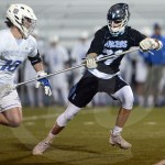 Junior Tommy Pollock tries to cross check a Rockhurst player and get the ball. Photo by Julia Percy