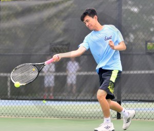 Junior Harvey Ji hits a forehand while warming up with his teammates before the match. Photo by Ally Griffith