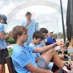 Members of the JV tennis team watch their teammates compete in doubles matches. Photo by Ally Griffith