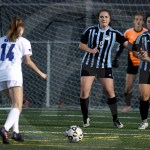 Junior Karoline Nelson, senior Emily Cooper and junior Isabella Velez prepare to block a penalty kick. Nelson was successful in diverting the ball. Photo by Kate Nixon