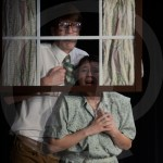 """Senior Davis Vaughn and sophomore Mazey Heim play the mom and dad in """"Life After Elvis"""". They were looking out the window to watch Elvis get in trouble. Photo by Elle Karras"""