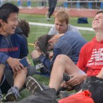 Freshman Charlie Duchene hurts his leg and tries to stretch it, while freshman Tongtong Yi laughs. Photo by Elle Karras