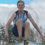 Freshman Alex Blickhan is in mid-air while competing in the long jump. Photo by Elle Karras