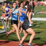 Sophomore Kate Kowalik hands the baton off to junior Brooklyn Beck in their relay race. Photo by Annakate Dilks