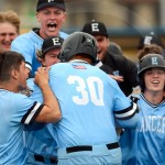 The team jumps on senior Noah Steele after he helps clinch the game winning runs. Photo by Megan Biles