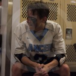 Senior Charles Boerger sits down and cools off in the locker room during halftime. Photo by Noelle Griffin