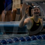 After looking at her time for the 100 yard breaststroke on the board, freshman Maeve Linscott celebrates. Linscott finished in fifth with a finals time of 1:07.39. Photo by Kate Nixon