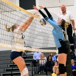 Freshman Vivian Riehl blocks the ball from coming over the net.