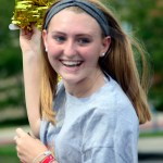 Sophomore Sadie McDonald runs with the streamers for the float. Photo by Bella Wolfe