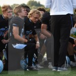 After their loss against the Cougars, the team kneels while their coach speaks. Photo by Noelle Griffin